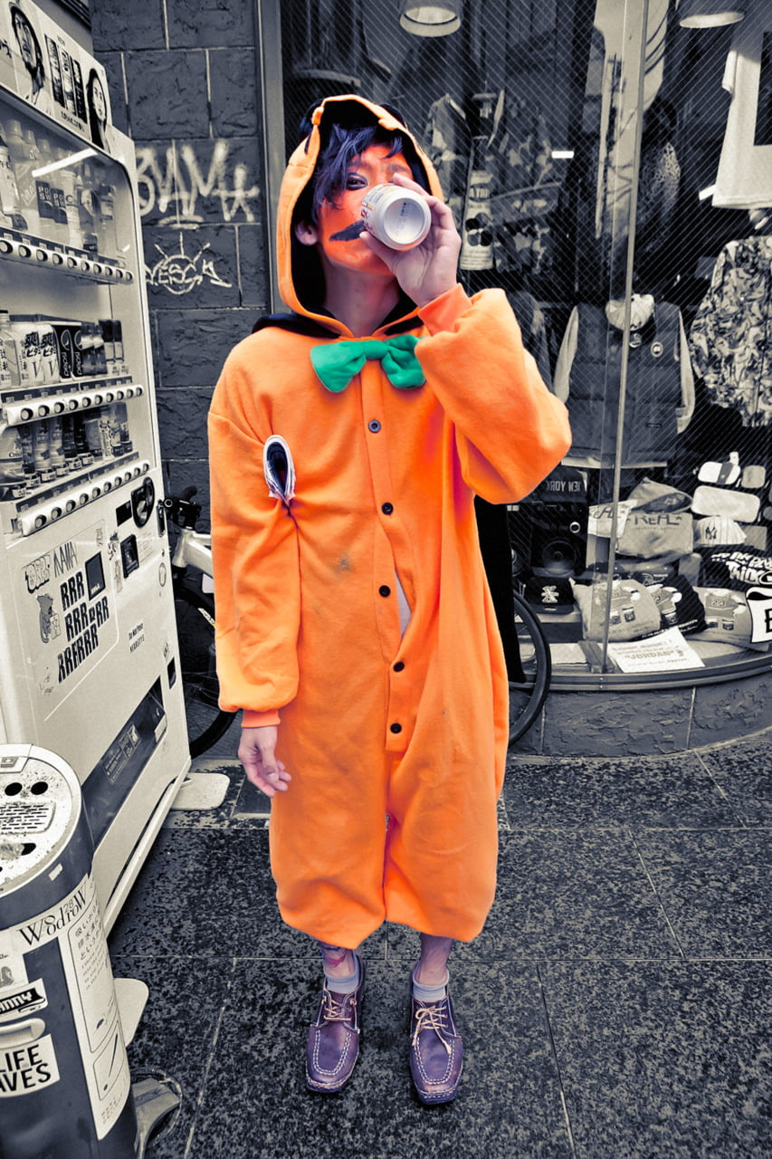 Japanese guy wearing pumpkin orange kigu PJs with some orange paint at his face on Halloween.